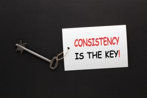 """An image of a key tied to a paper that says """"Consistency is the key!"""""""