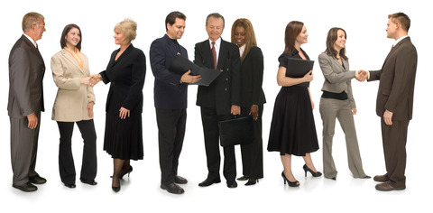 A photograph of multiple people in suits talking and networking.